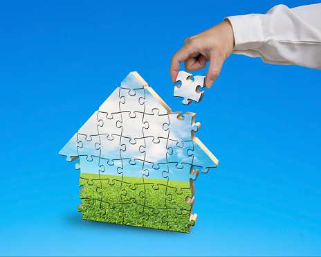 Assembling puzzles in house shape isolated in blue background
