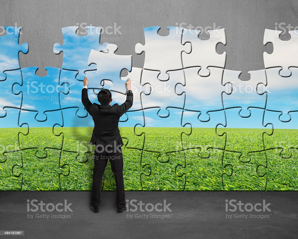 Assembling puzzles to instead of beautiful landscape with wall stock photo