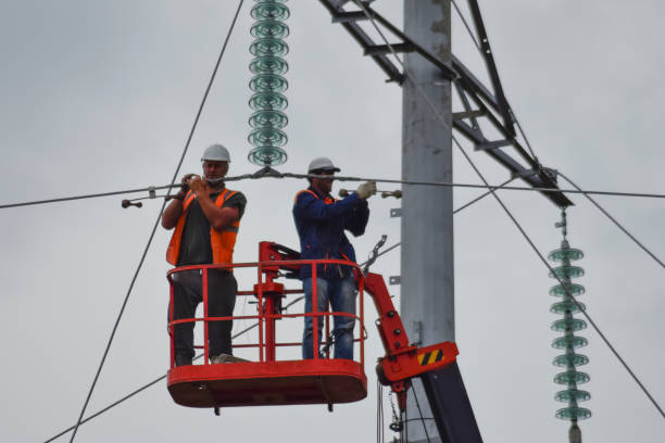 Assembly and installation of new support of a power line Russia, village Poltavskaya - June 23, 2015: Power line support, insulators and wires. Appearance of a design. Assembly and installation of new support and wires of a power line. football lineman stock pictures, royalty-free photos & images