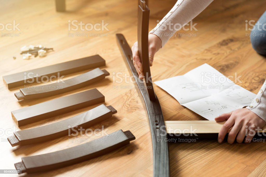 Assembly of wooden furniture, a woman putting together the wooden parts of the dining chair, using instruction. and a furniture screw and allen key. stock photo