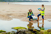 Two females working on the beach by a pool of water collecting and analysing samples. They are wearing protective gloves and reflective clothing