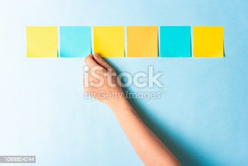 1090161334 istock photo Assessment analysis evaluation concept. Hand choosing multi colored notes on blue background. 1069854244