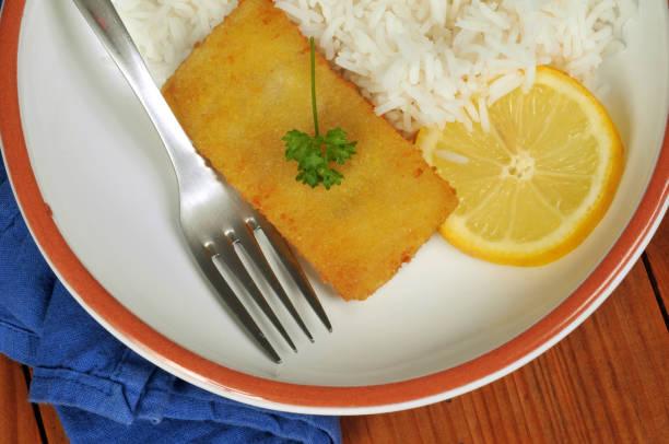 Assiette de poisson pané avec du riz Assiette de poisson pané avec du riz  et une rondelle de citron vue de dessus riz stock pictures, royalty-free photos & images