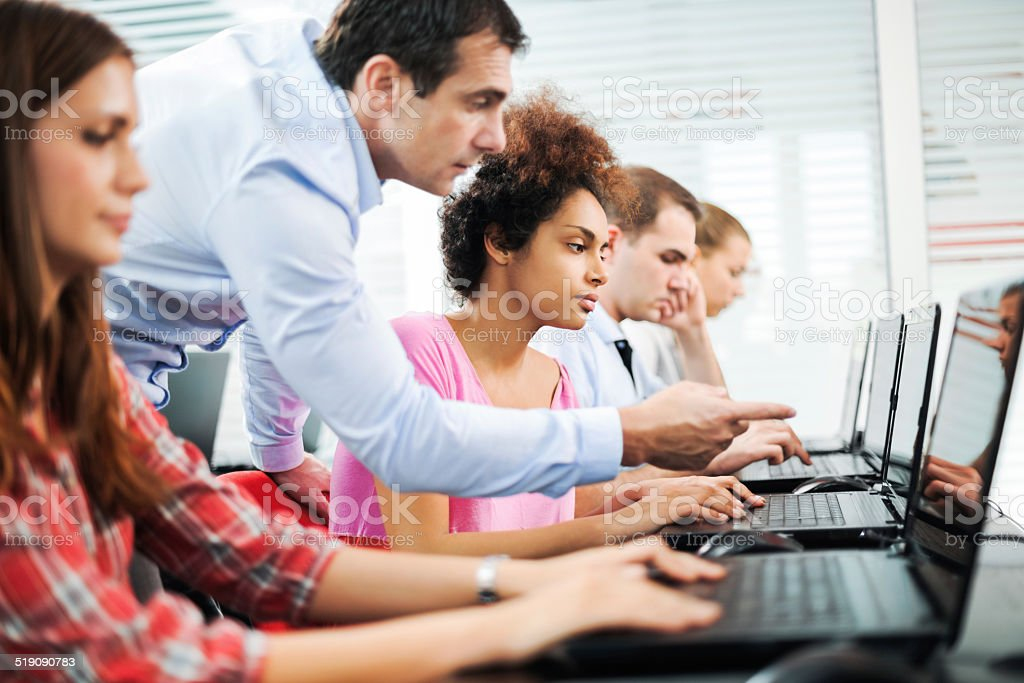 Assistance at computer class. stock photo