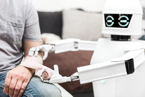 Hilfemedizinserviceroboter Setzt Einen Verband Auf Einem Arm Eines Männlichen Patienten Zu Hause Im Schlafzimmer Stockfoto und mehr Bilder von Anthropomorph