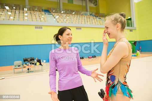 istock Assistant and Young Rhythmic Gymnastics Athlete Socializing at Training 958493546