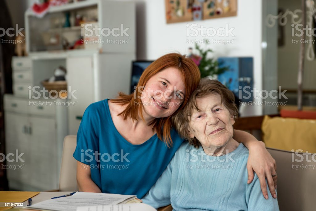 Assistant at Nursing Home Hugging Senior Woman stock photo