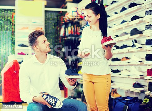 istock Assistant helping customer to choose sneakers 1027847238