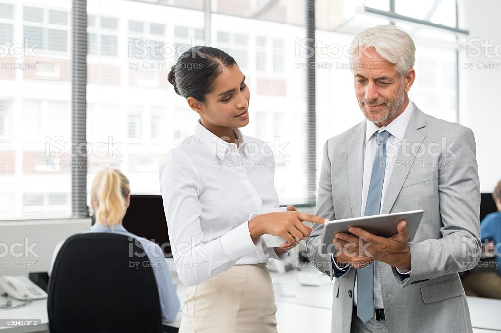 Assistant helping senior businessman stock photo