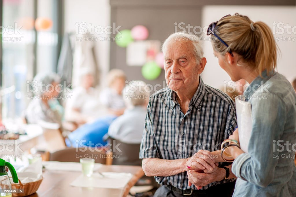 Assistant In The Community Center Giving Advice To A Senior Man stock photo