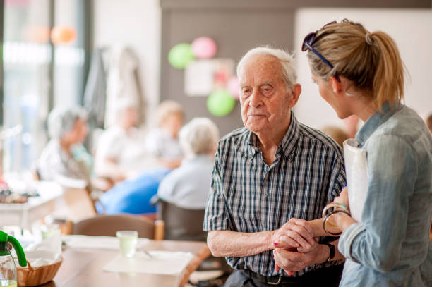 assistant in the community center giving advice to a senior man - fragility stock pictures, royalty-free photos & images