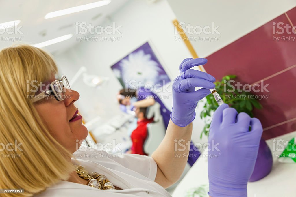 Assistant Preparing Anesthesia stock photo
