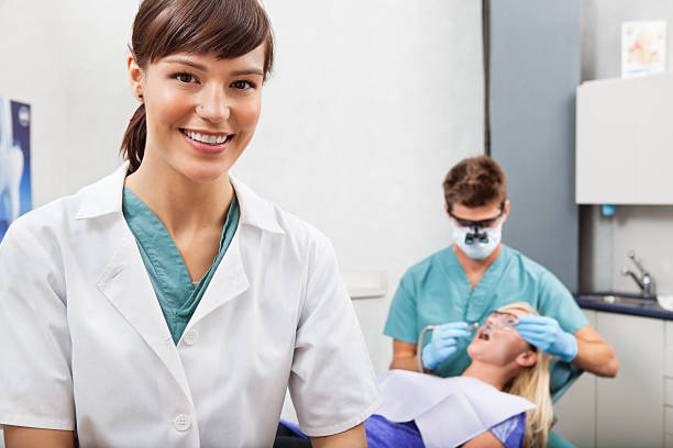 assistant with dentistry work in the background - dental assistant stock photos and pictures