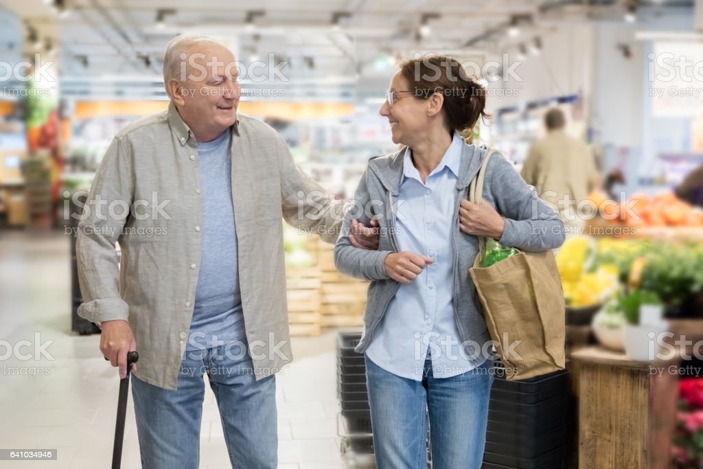 Assisted living - senior man with caregiver shopping stock photo