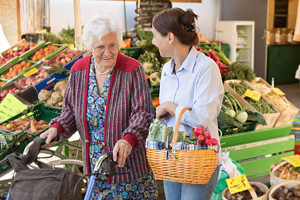 Assisted living - senior woman with caregiver shopping stock photo