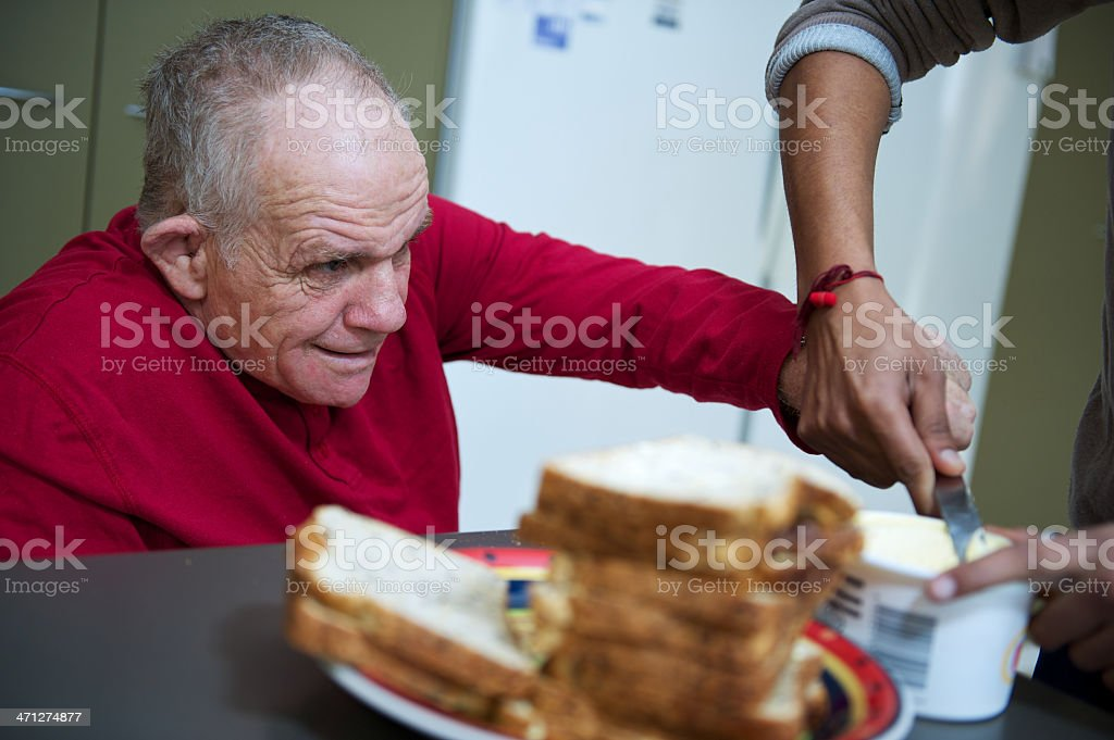 Assisting a man to spread butter stock photo