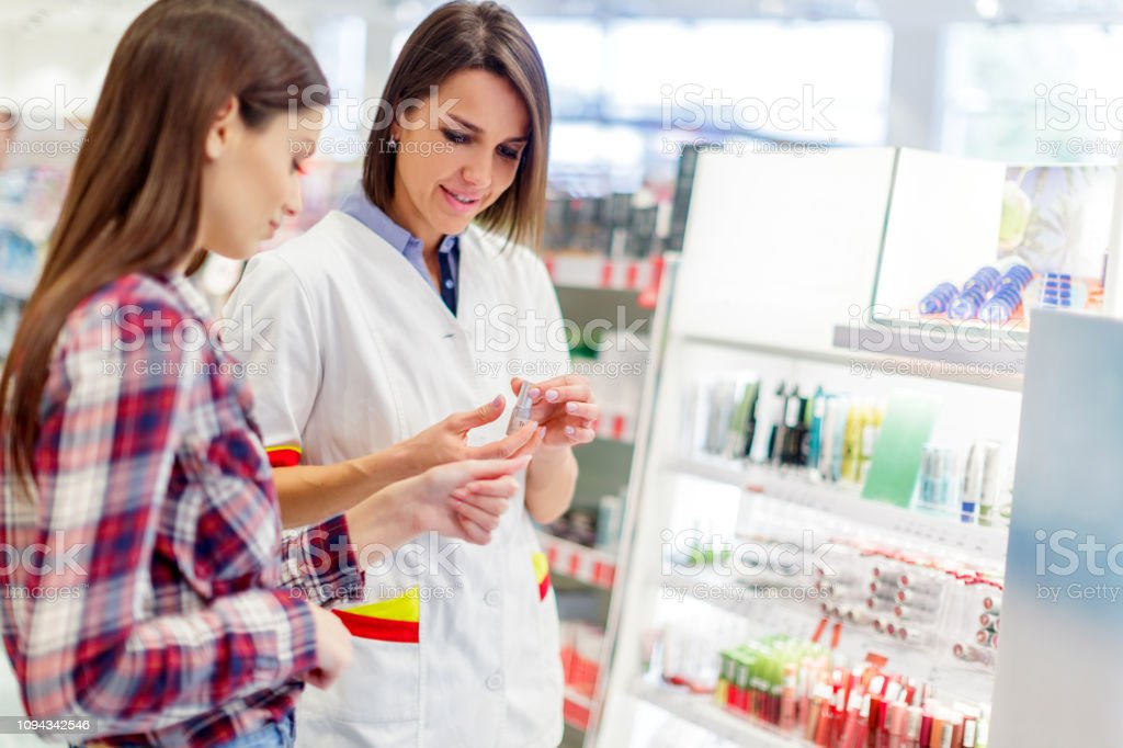 Assisting customer choose lipstick stock photo