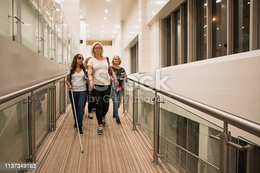 A front-view shot of a small group of women walking down a disabled access ramp in an airport, two women are visually impaired and one woman can be seen holding a cane.