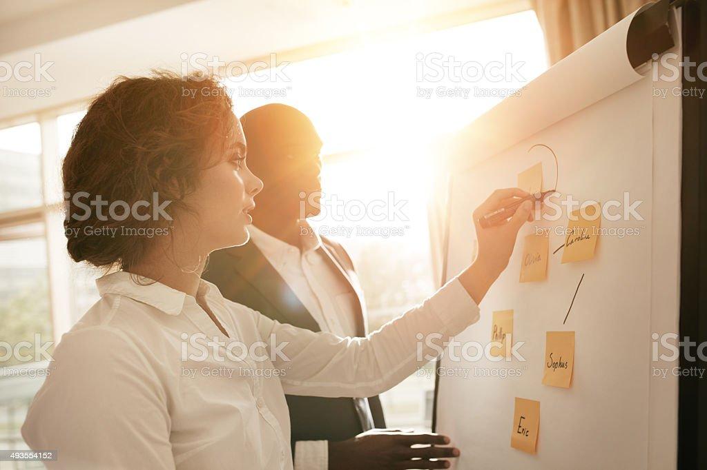 Employés travaillant ensemble de dessin sur le tableau à feuilles - Photo