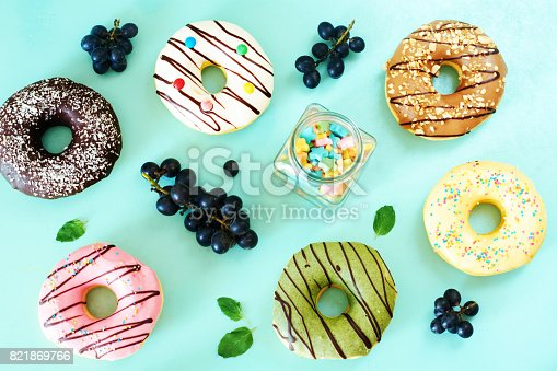 Vanilla, chocolate, strawberry, caramel, pictachio donuts, grape and candy. Top view.