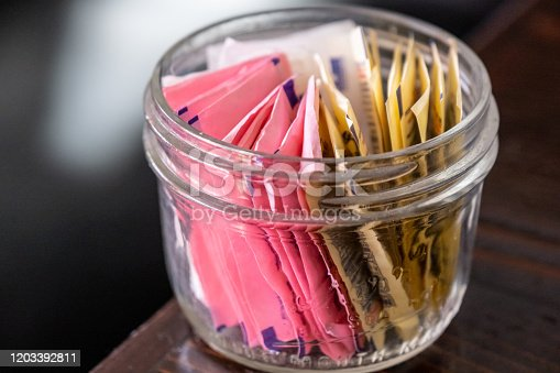 small glass bowl full of assorted artificial sweetener envelopes