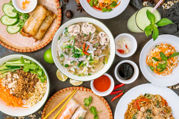 assorted asian dinner, vietnamese food. pho ga, pho bo, noodles, spring rolls - pho soup stock photos and pictures