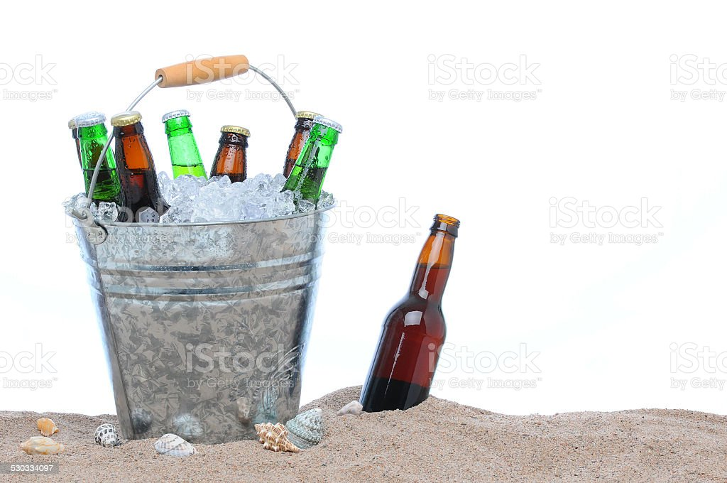 Assorted beer bottles in bucket of ice in the sand stock photo