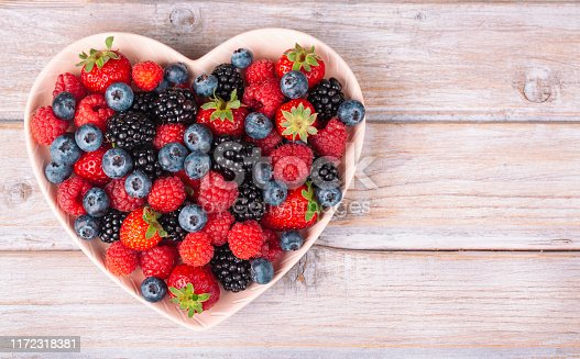 Assorted berries in a heart plate on white rustic wooden table