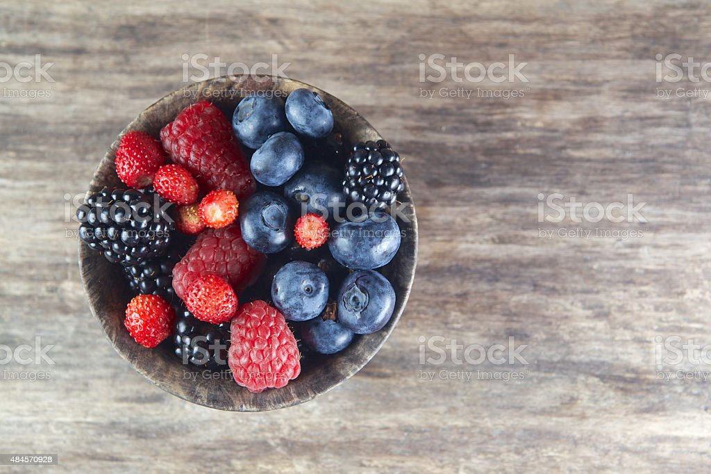 Assorted berries in bowl on wood stock photo