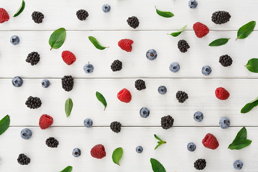 istock Assorted berries on white wooden table top view 859662642