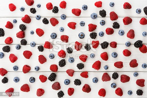 istock Assorted berries on white wooden table top view 862271422
