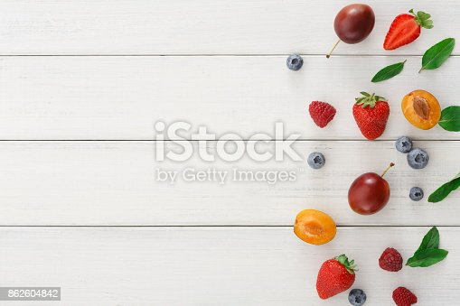 862604802 istock photo Assorted berries on white wooden table top view 862604842