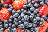 Assorted blueberries and strawberries in a white dish, sleek focus, different angles, close-up