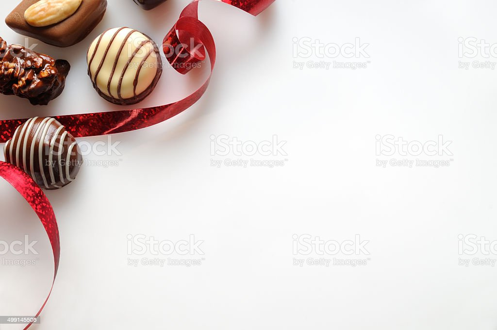 Assorted bonbons with red ribbon on a white table Top stock photo
