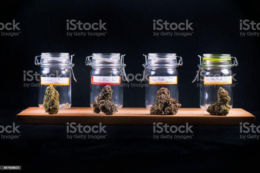 Assorted cannabis bud strains and glass jars - medical marijuana dispensary concept stock photo