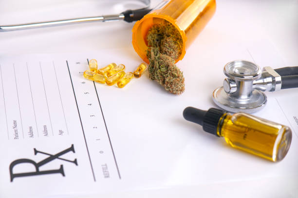 Assorted cannabis products, pills and cbd oil over medical prescription sheet stock photo