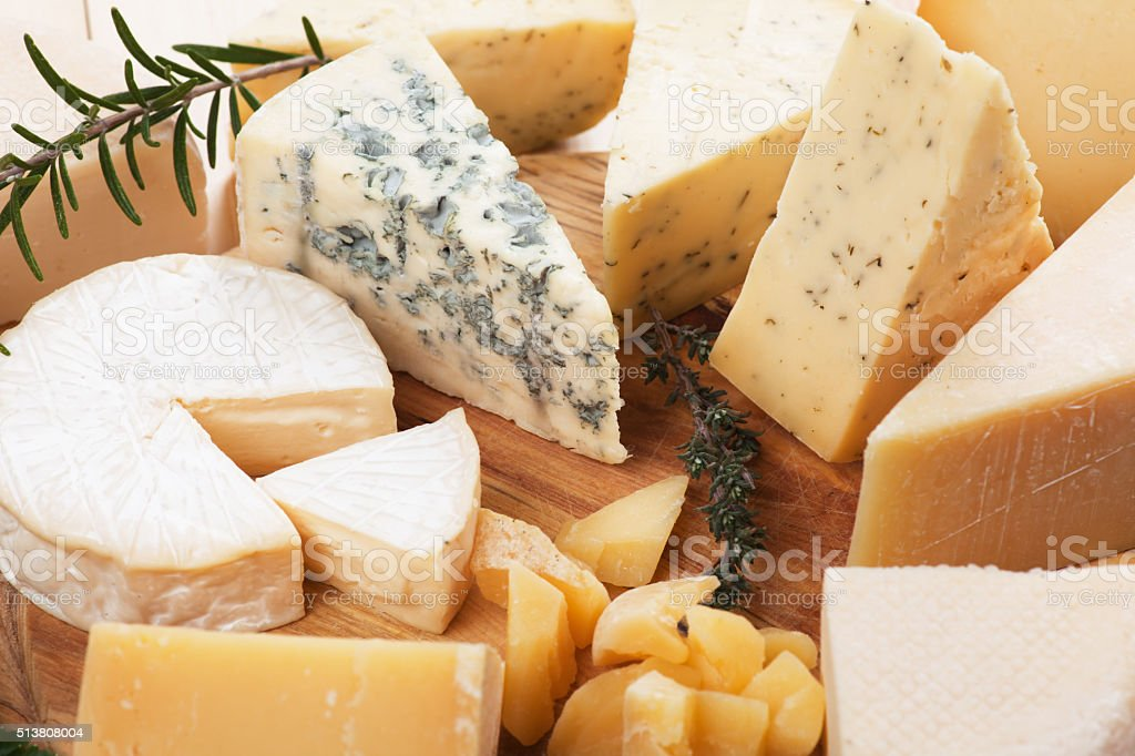 Assorted cheese on wooden platter stock photo