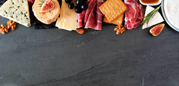 Assorted cheeses and meat appetizers, above view top border banner on a dark stone background with copy space stock photo