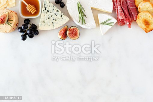 Assorted cheeses and meat appetizers. Top border, overhead view on a white marble background with copy space.