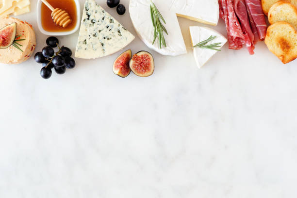 Assorted cheeses and meat appetizers, overhead view top border on a white marble background with copy space stock photo