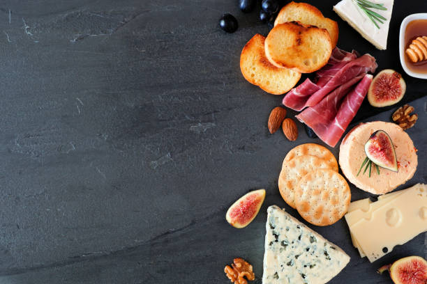 Assorted cheeses and meats, top view side border on a dark background with copy space stock photo