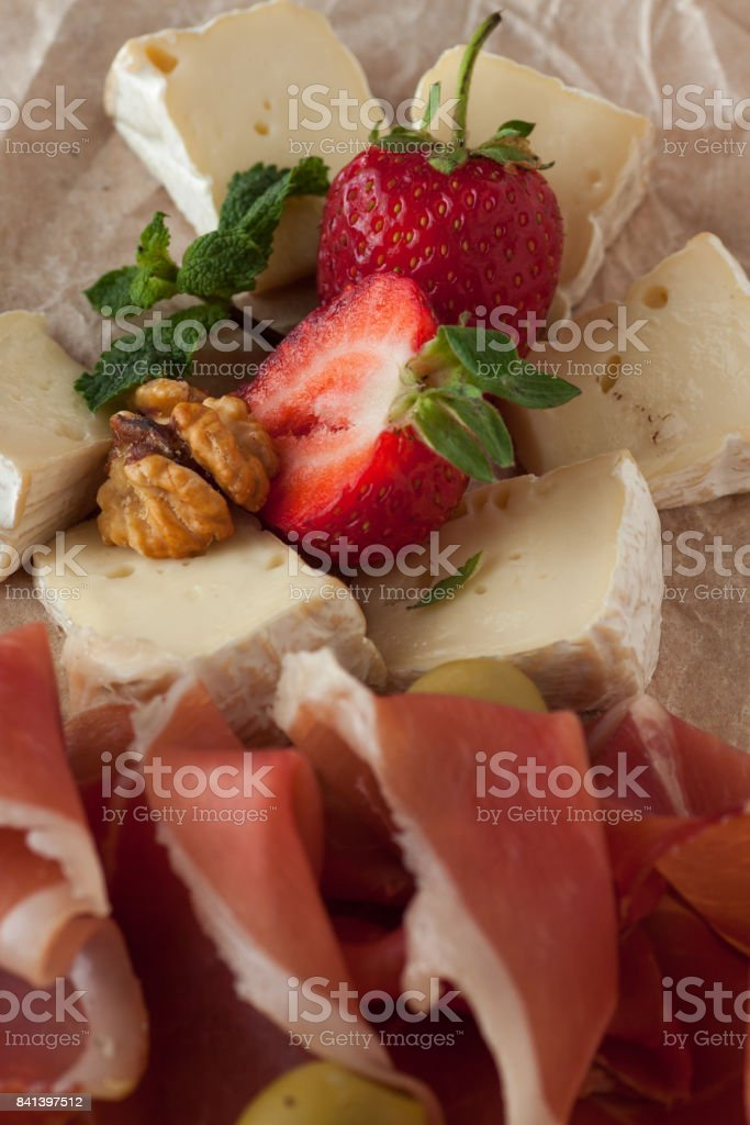 Assorted cheeses and prosciutto stock photo