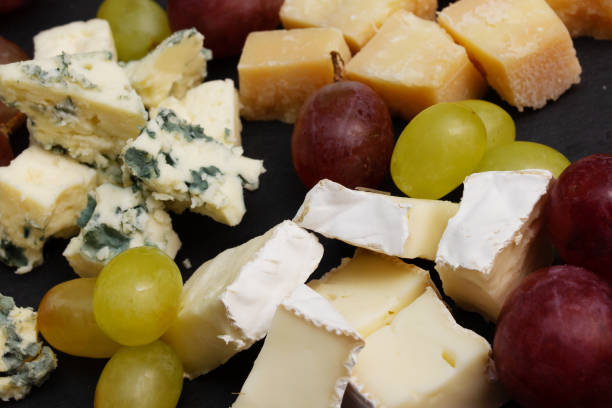 Assorted cheeses on a black plate stock photo
