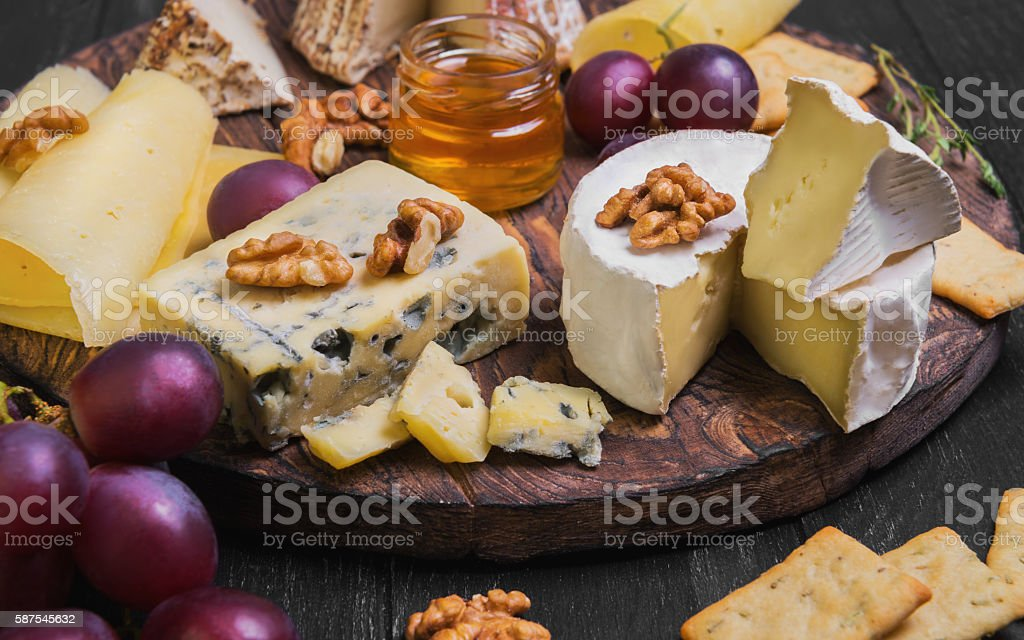 Assorted cheeses on round wooden board plate stock photo
