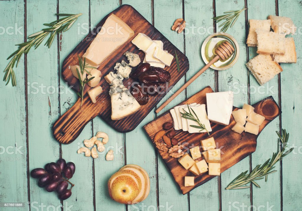 Assorted cheeses on wooden board plates served with nuts, grapes, bread, honey, and dates on shabby chic wood background, top view. stock photo