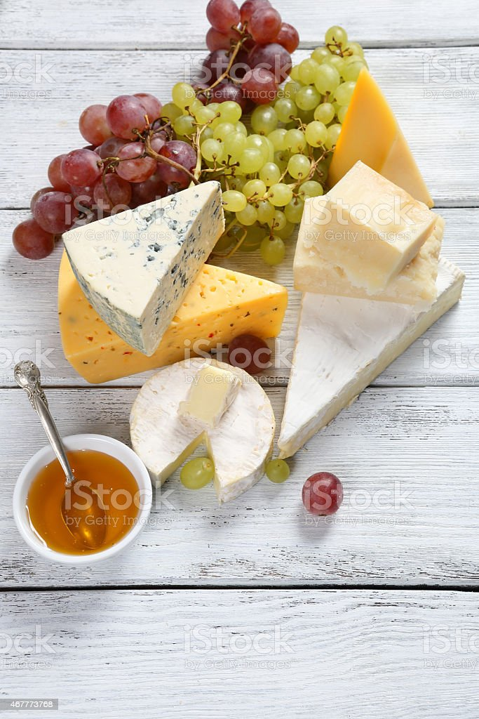 Assorted cheeses with grapes and honey stock photo