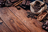 Assorted chocolate and roasted coffee beans in old fashioned style placed on top of a wooden table in rustic kitchen with copy space in frame