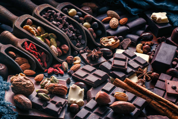 assorted chocolate, nuts and dried fruit in old fashioned style - потакание своим желаниям стоковые фото и изображения