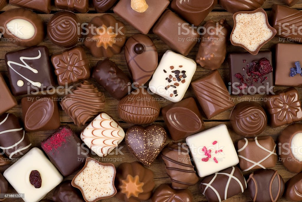 Assorted chocolate pralines on wooden background stock photo