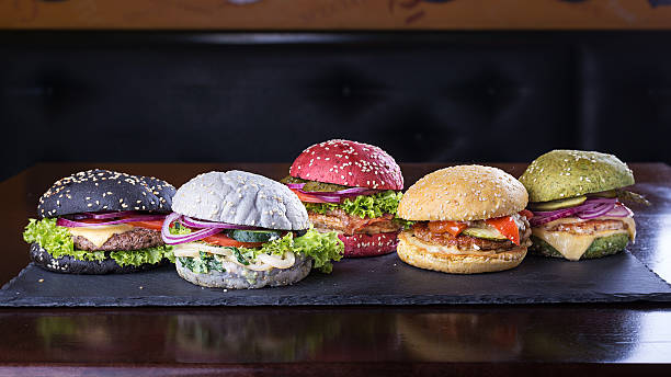 Assorted colored burgers Assorted colored burgers with different fillings, with sesame seeds on slate blackboard sweet bun stock pictures, royalty-free photos & images